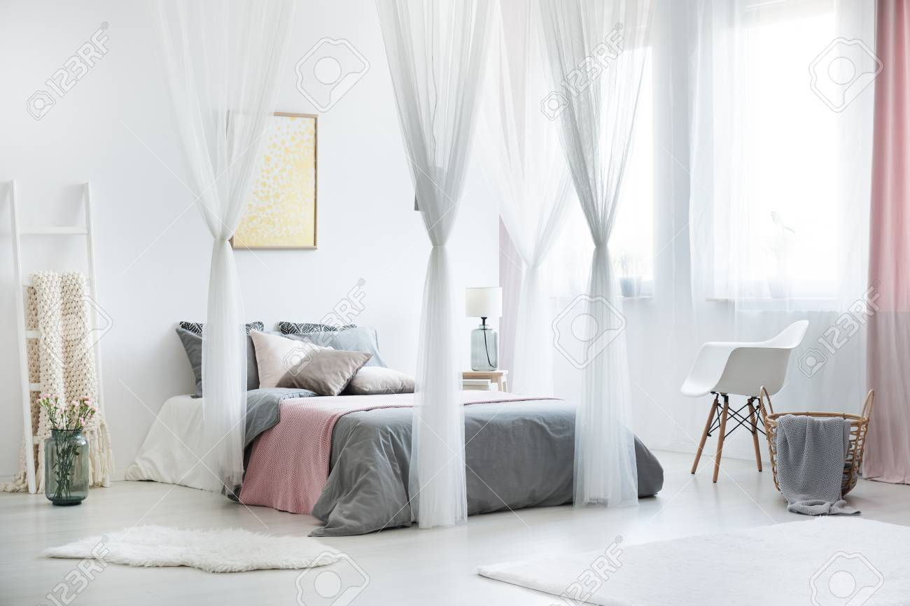 White Chair Next To Bed With Canopy In Cozy Bright Bedroom Interior ...