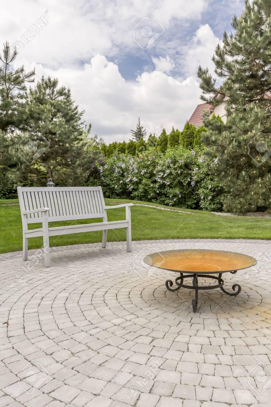 Tabla De Diseñador En Terraza Con Banco Blanco Al Lado De La Hierba Y árboles