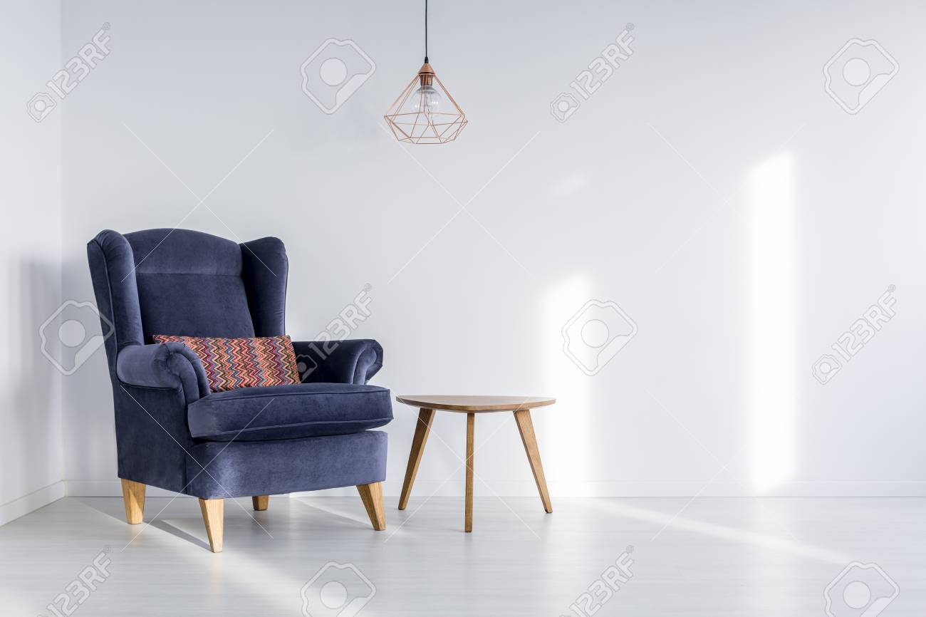 Copper Lampshade Hanging Above Dark Blue Armchair With Colorful