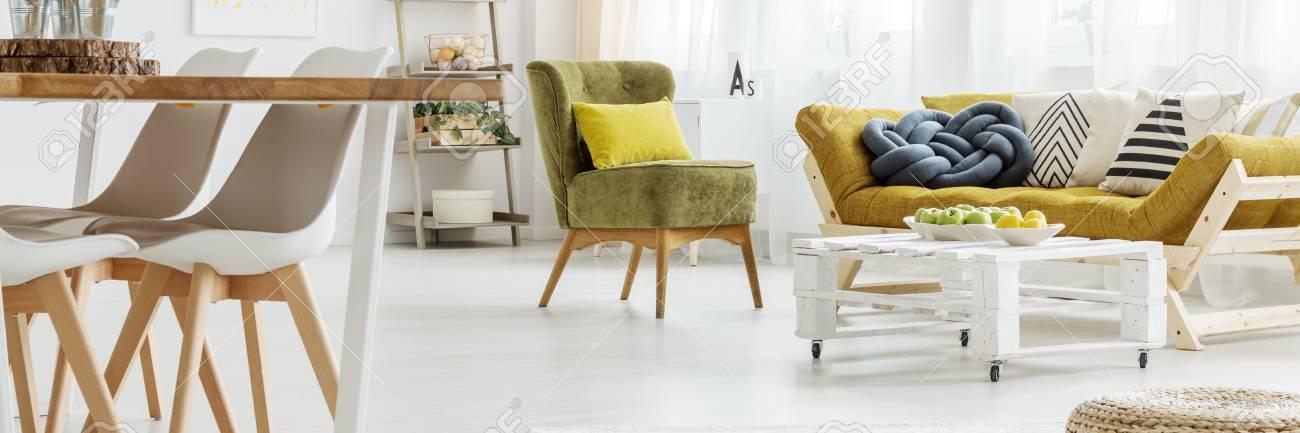 Colorido sofá con mesa de centro y mesa de comedor de madera en el salón