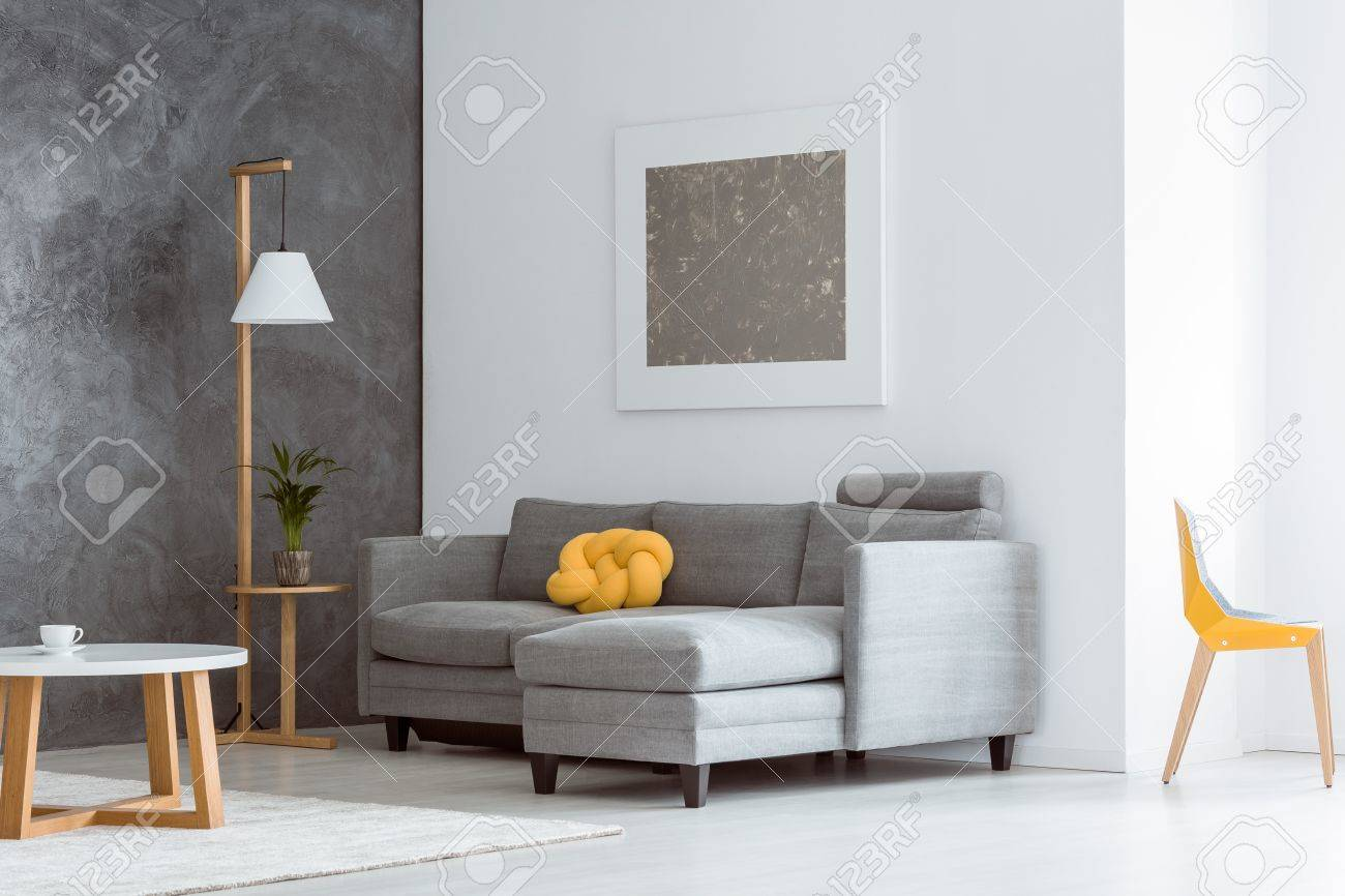 Couleur Salon Gris Et Blanc accent de couleur jaune canari dans un intérieur de salon ouvert simple  avec un canapé gris, un mobilier en bois moderne et une peinture abstraite  sur