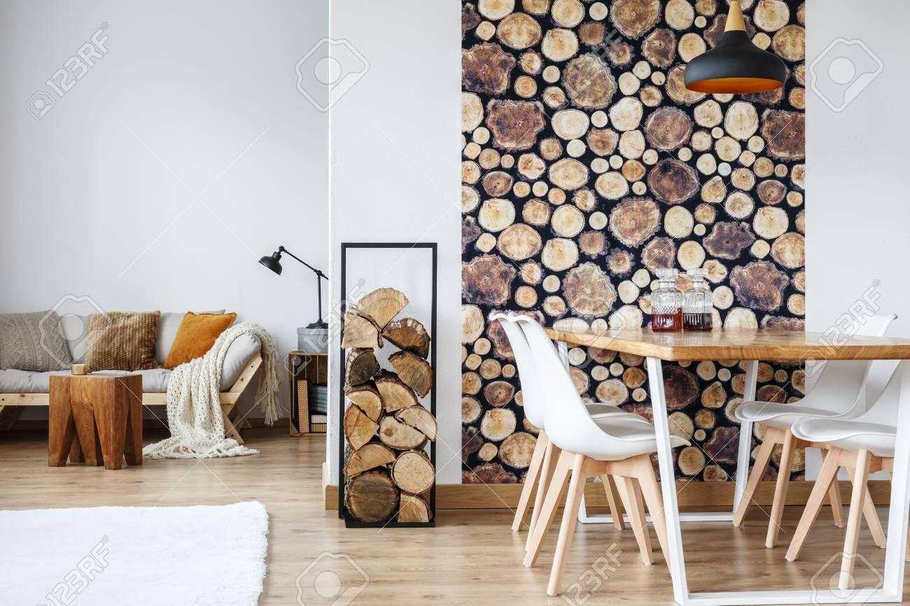 Luminoso y cálido salón con sofá beige, mesa de comedor y troncos de madera  decorada