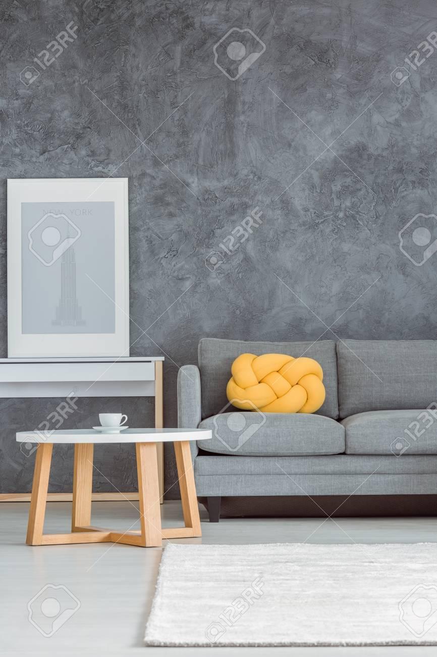 Beau salon simple avec mur gris, canapé confortable, table basse blanche et  en bois, console, affiche, tapis et coussin décoratif jaune