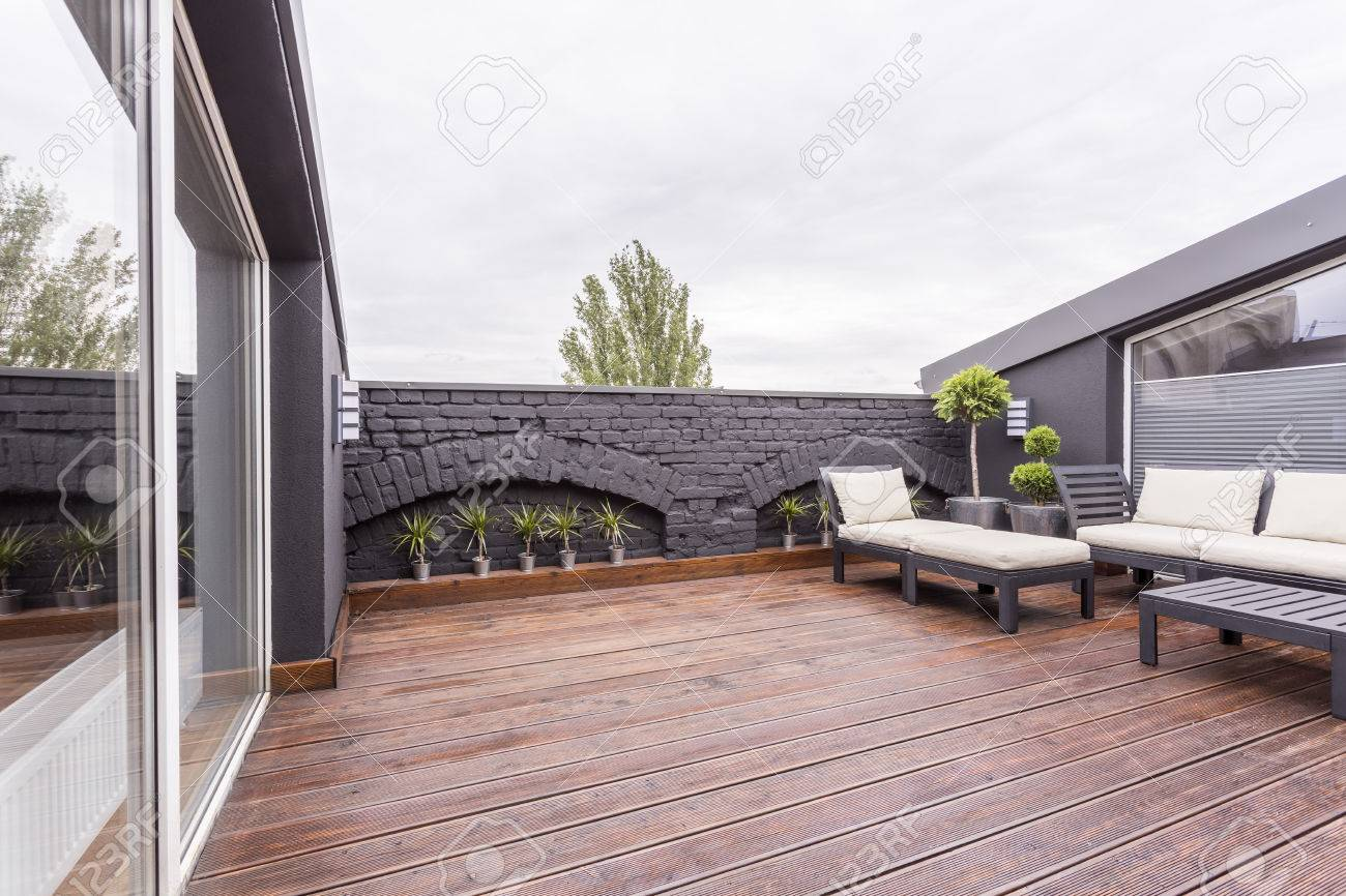 Terraza Con Muebles De Jardín En El Piso De Madera Oscura Y Plantas Contra La Pared De Ladrillo Negro