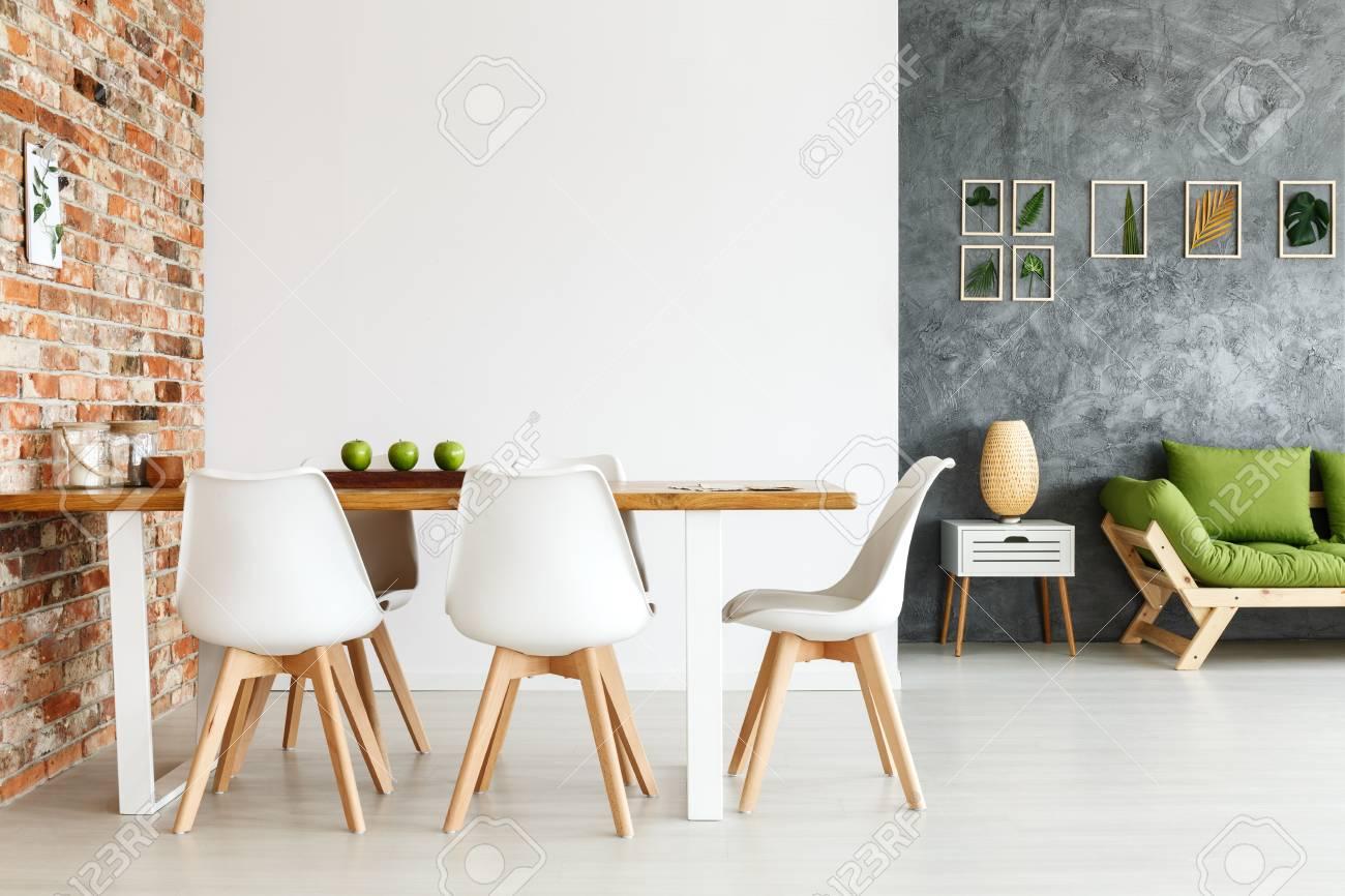 Diseño interior contemporáneo de comedor con mesa independiente contra la  pared de ladrillo y sala de estar decorada con sofá inteligente y ...