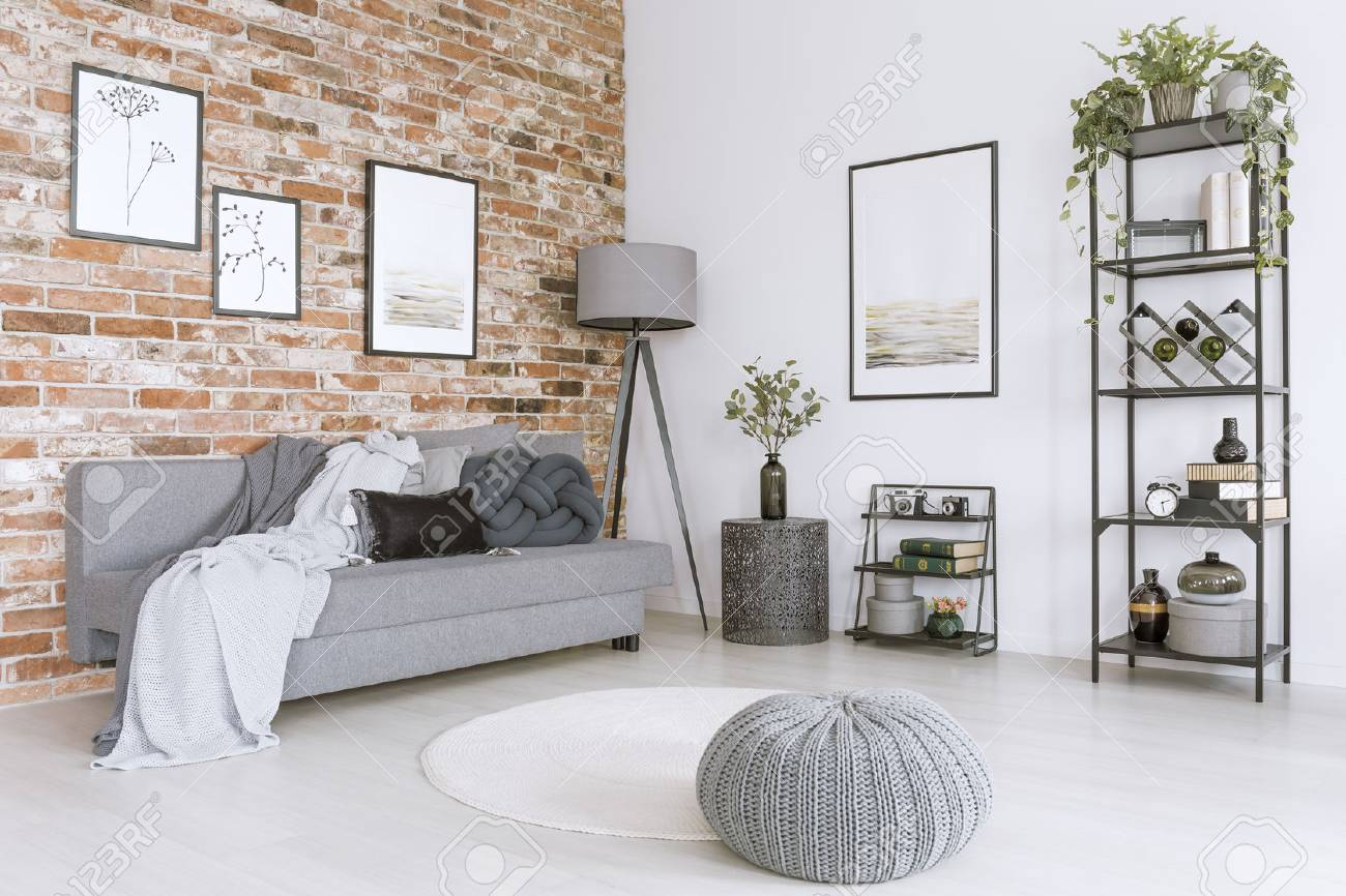 White and gray living room with knit pouf, round rug and modern,..