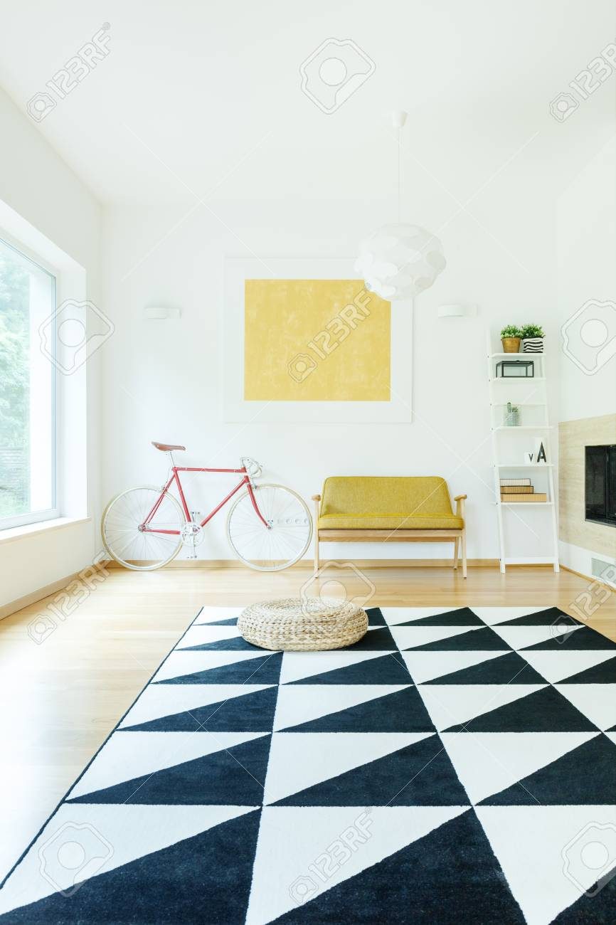 Stock photo triangle carpet in spacious contrast color interior with gold painting on wall above yellow sofa and red bike