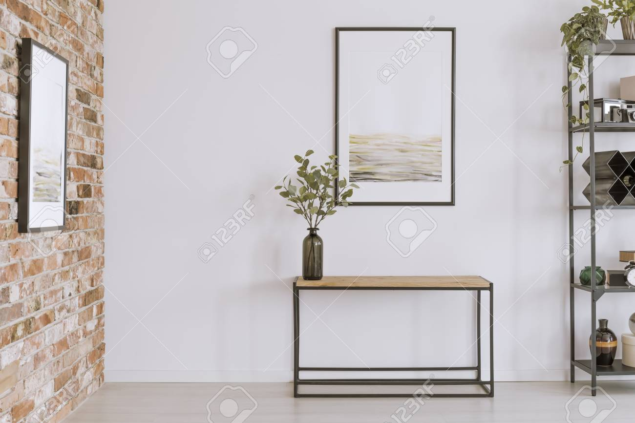 Simple Painting Above Wooden Console Table With Twigs In A Glass Vase In  Modern Living Room
