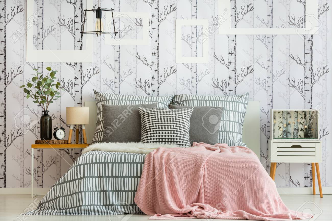 Feminine bedroom interior with forest inspired decorations and geometric bedding - 88438038