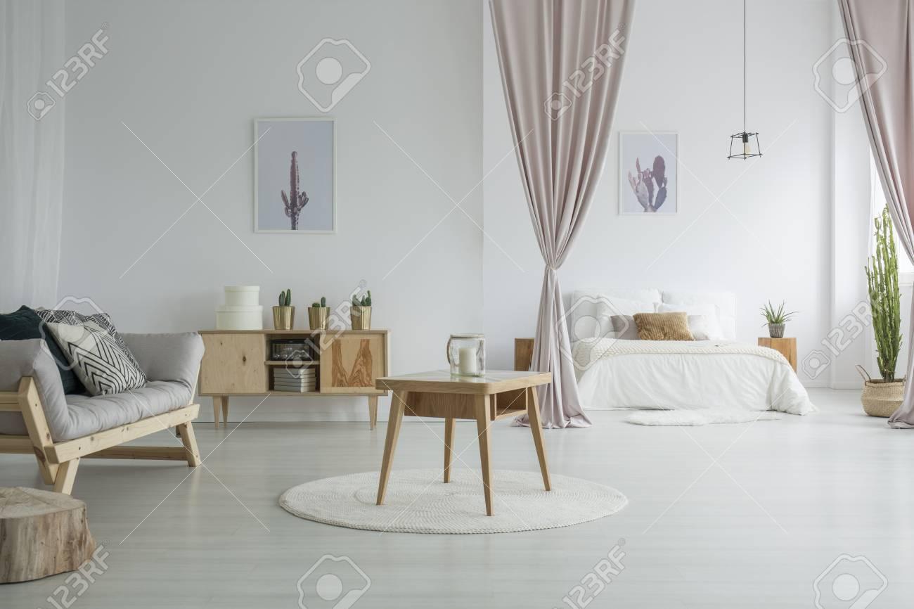 Grand salon avec table en bois sur tapis blanc, placard rustique et canapé  gris près de la chambre ouverte