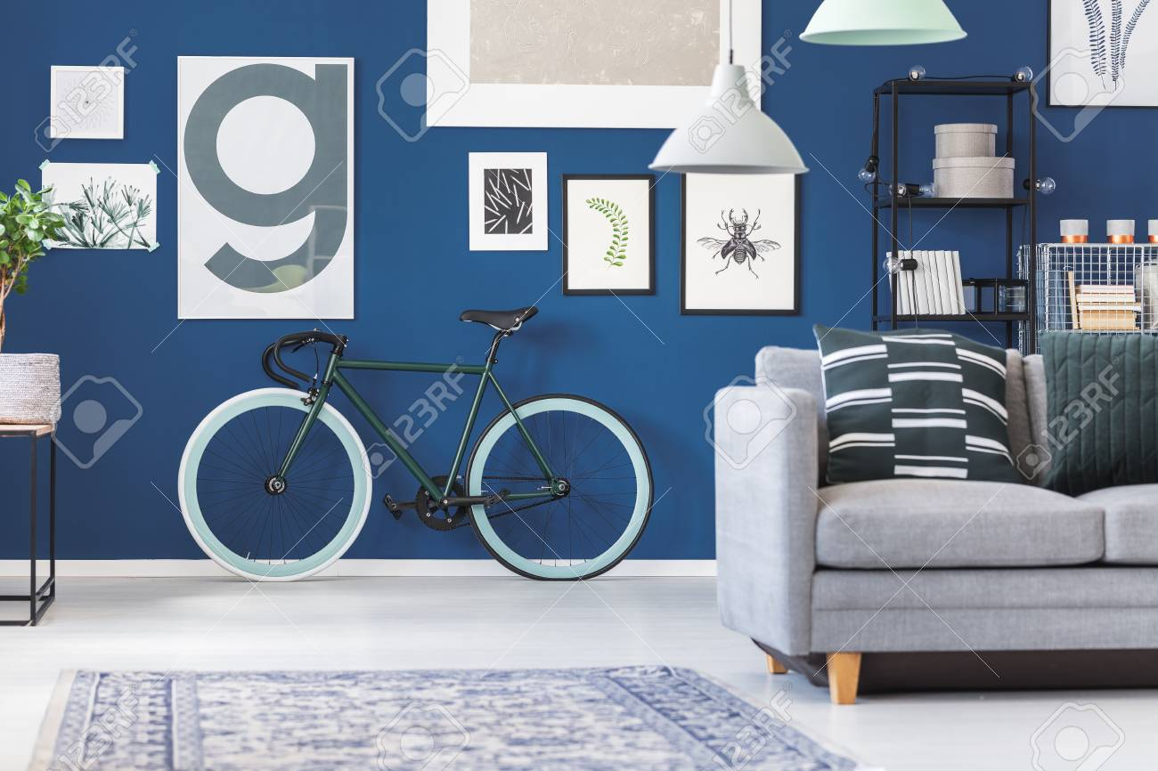 Black and green bike against dark blue wall with posters in living..