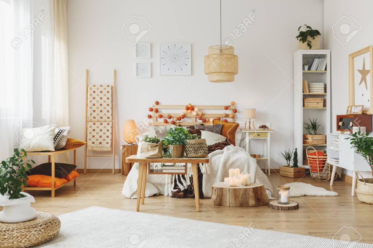 Belle chambre avec une petite table en face du lit double, et un grand  tapis couché sur le sol en bois