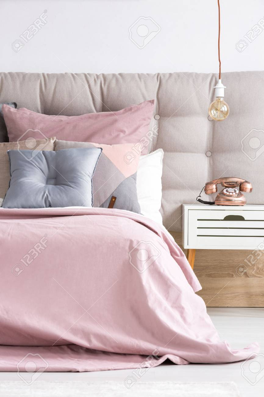 Comfortable bed with soft pink coverlet and decorative pastel..