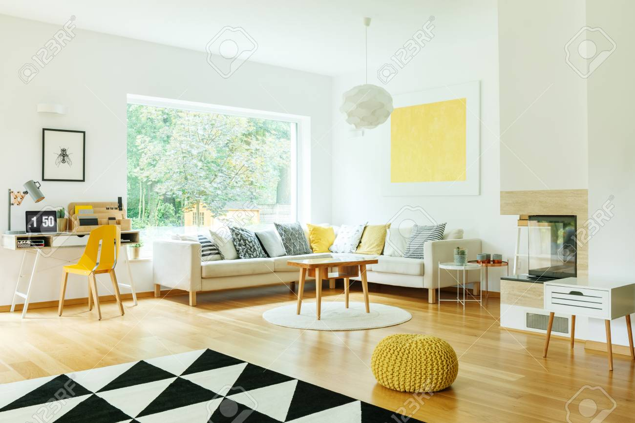 Wooden table on white round carpet in living room with yellow..