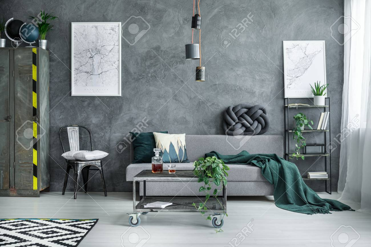 White pillow on black chair between metal wardrobe and grey sofa..