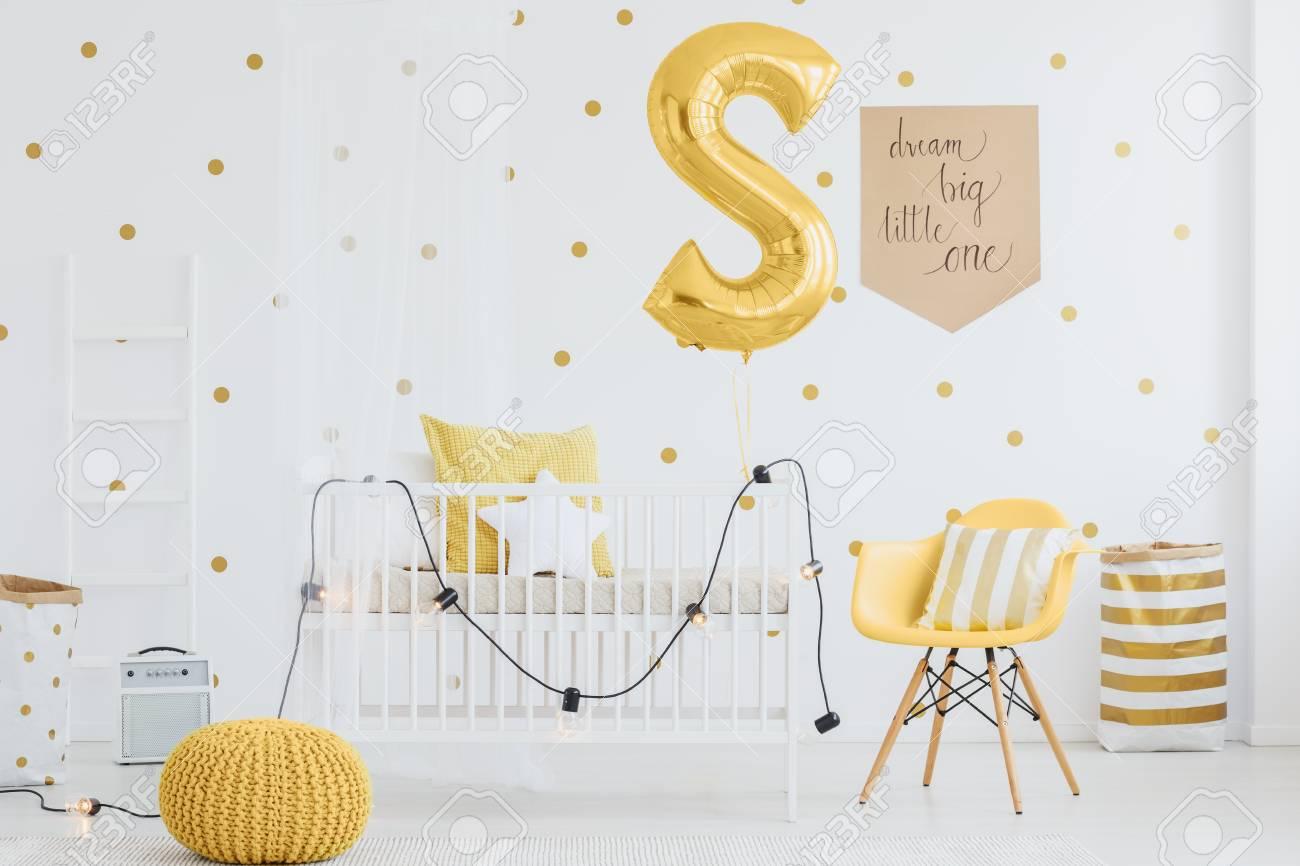 Pequeñas lámparas colgando en la cama de bebé de madera en la habitación  con detalles en amarillo