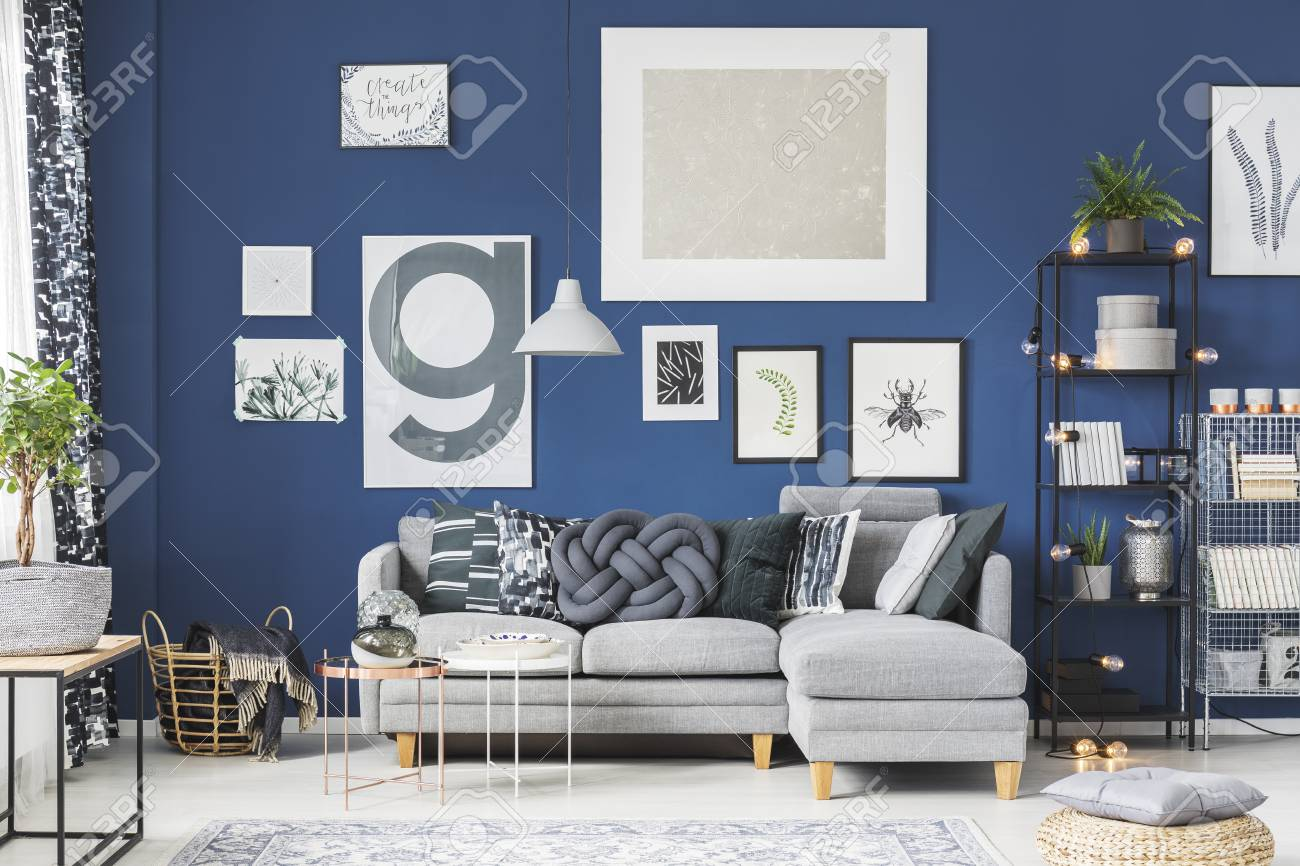 Grey corner couch against dark blue wall with posters in living..