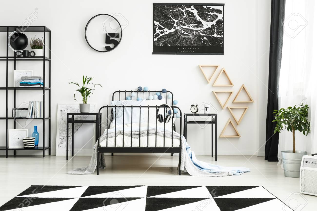 Monochromatic teenager\'s bedroom with round clock, black map..