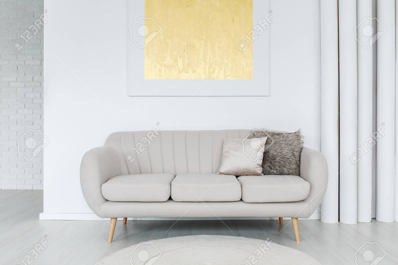 Gold Painting On The Wall Above Grey Sofa With Pillows In Bright
