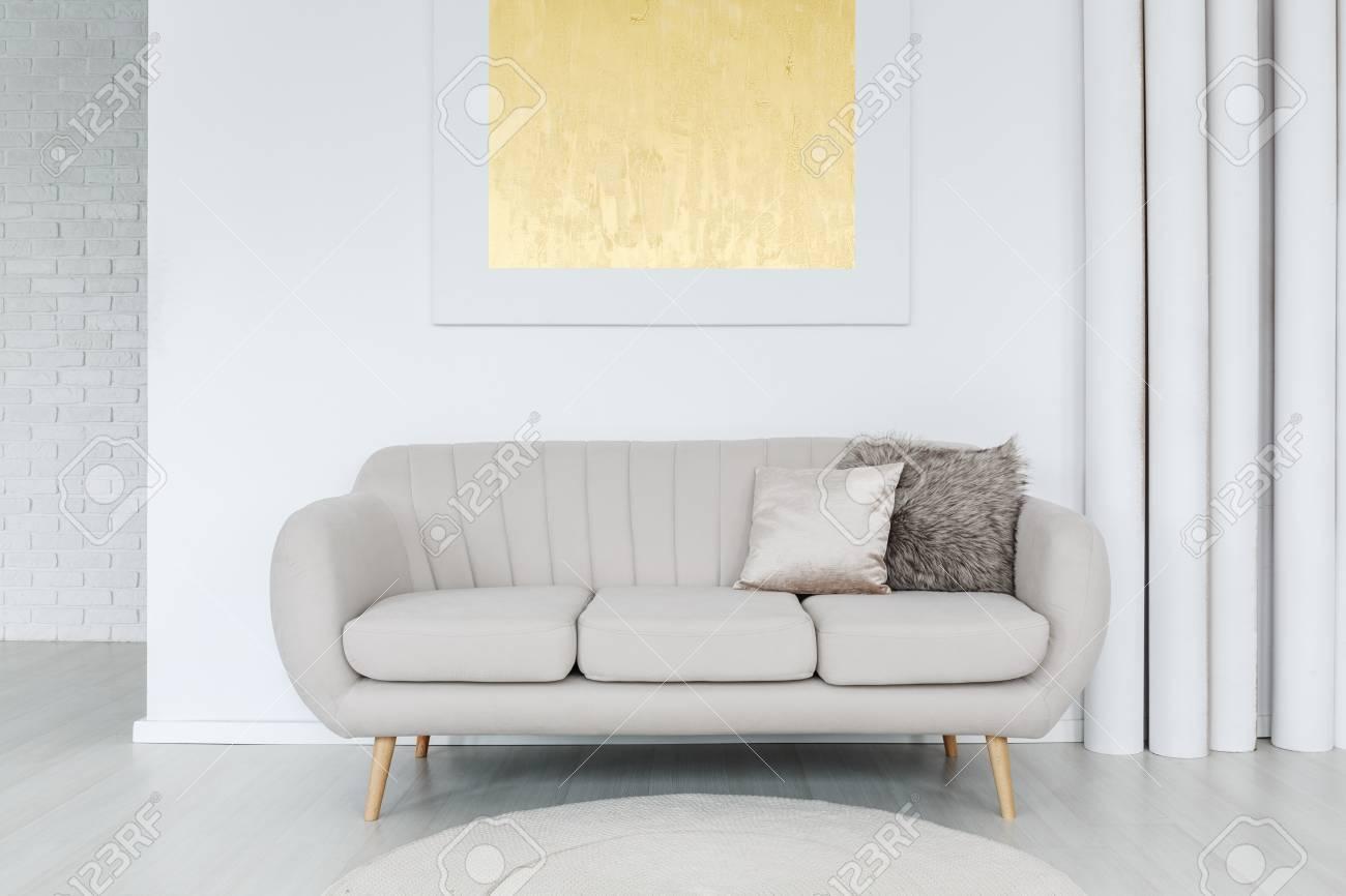 Peinture dorée sur le mur au-dessus d\'un canapé gris avec des oreillers  dans un salon lumineux avec une décoration en tube
