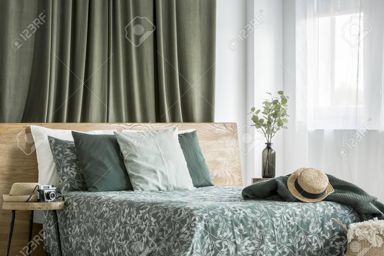 Chapeau Sur Une Couverture Vert Foncé Sur Un Lit King Size Avec Des
