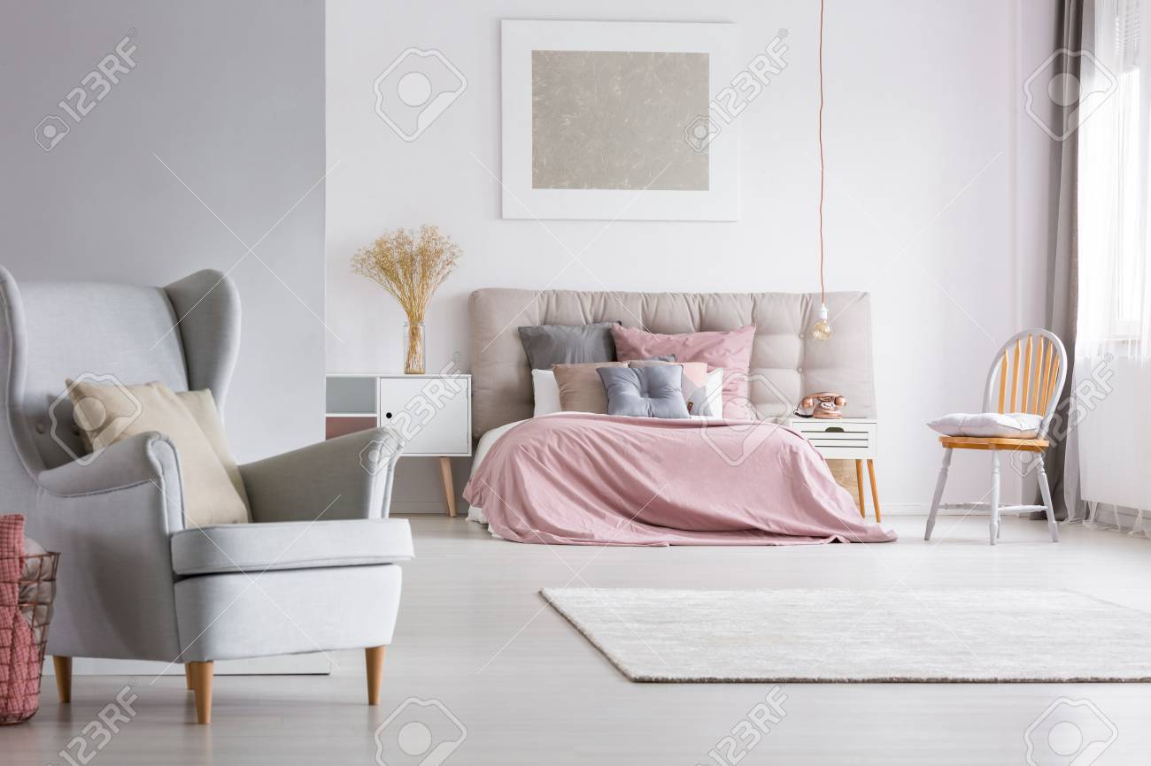 photo trendy armchair in cozy spacious interior of light pastel bedroom with scandinavian furniture pink q
