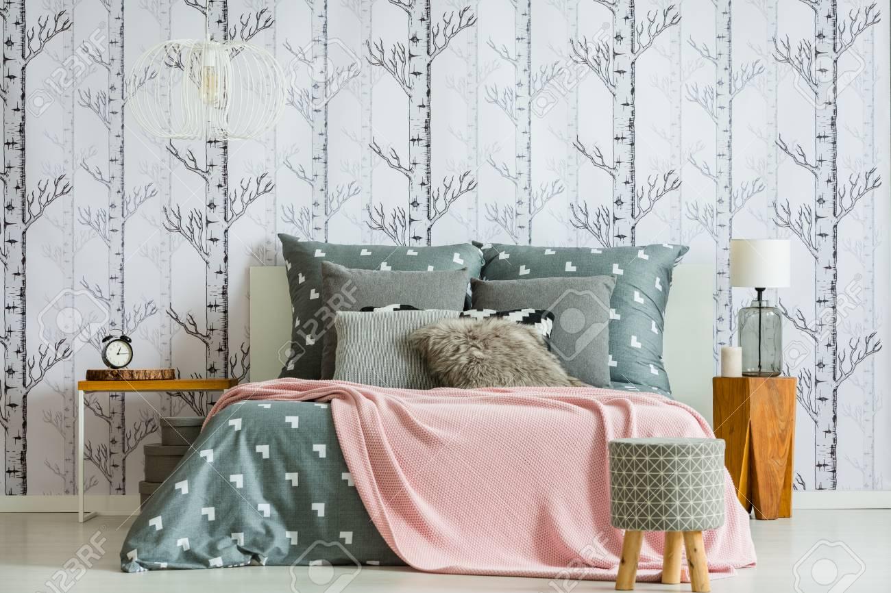 Designer tabouret devant le lit king-size avec couverture rose dans la  chambre à coucher avec lampe sur la table en bois
