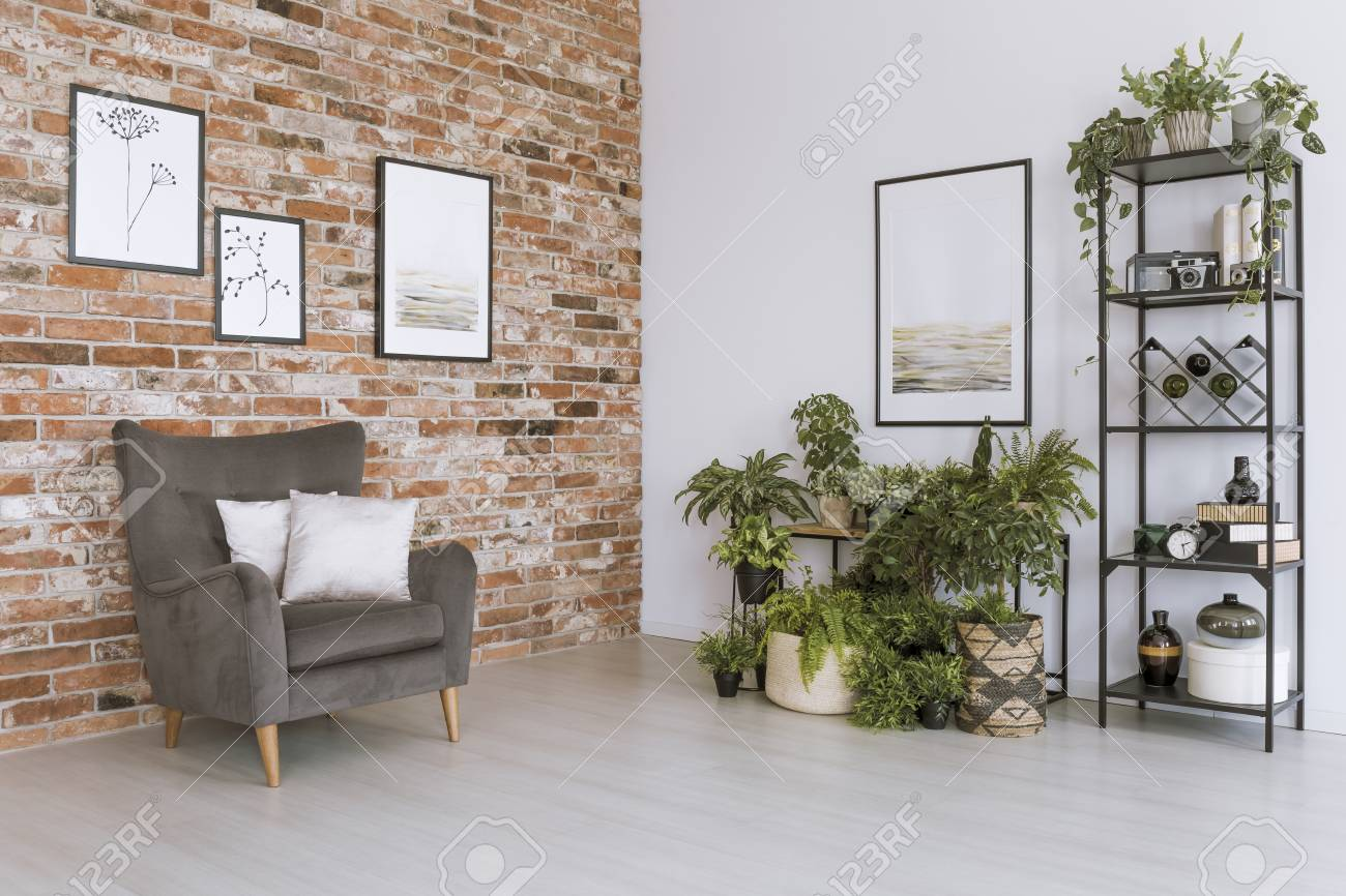 Poster On White Wall Above Plants In Simple Living Room With Grey Armchair  Against Brick Wall
