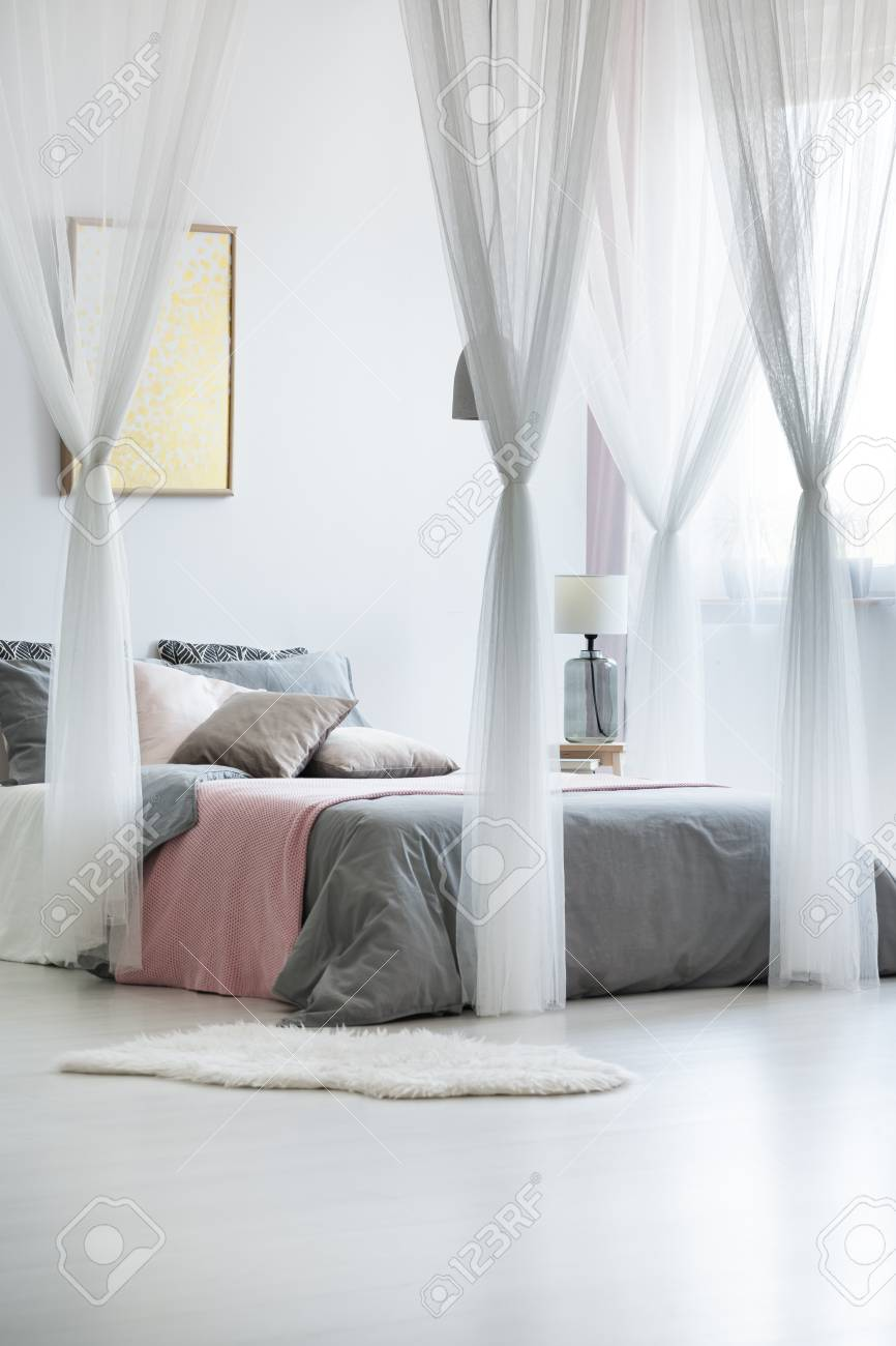 Artwork Above King Size Bed With Canopy Bed Drapes And Light Gray Bedding  With Pink
