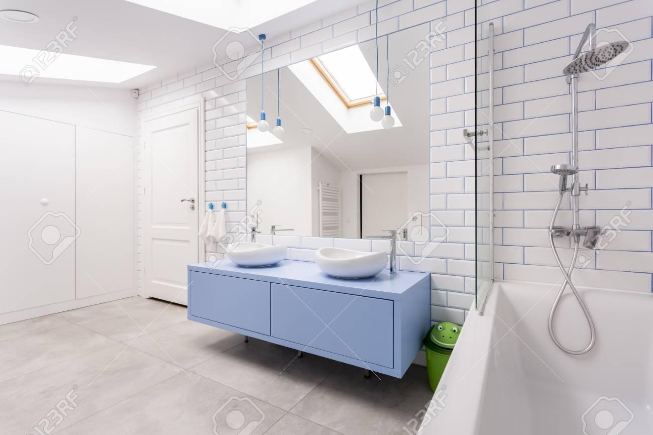 Set de douche en acier inoxydable et baignoire à côté du meuble vasque bleu  dans la salle de bain lumineuse mansardée