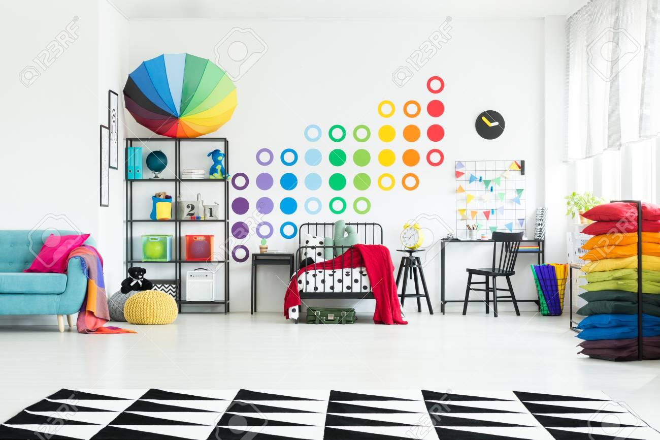 Chambre Enfant Bleu Et Rose oreiller rose sur le canapé bleu et un parapluie coloré sur une étagère  dans la chambre de l'enfant avec couverture rouge