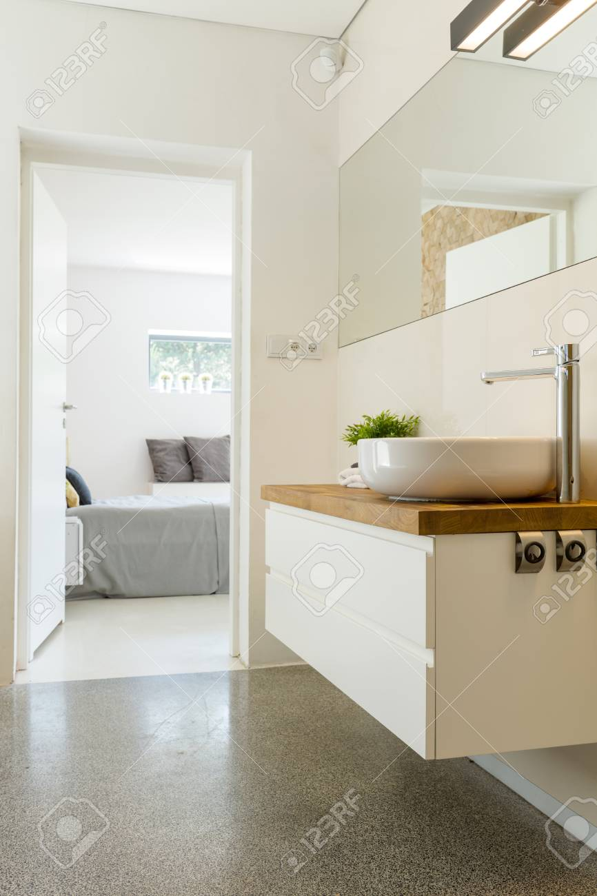 View From Elegant Bathroom With Sink And Mirror On Master Bedroom