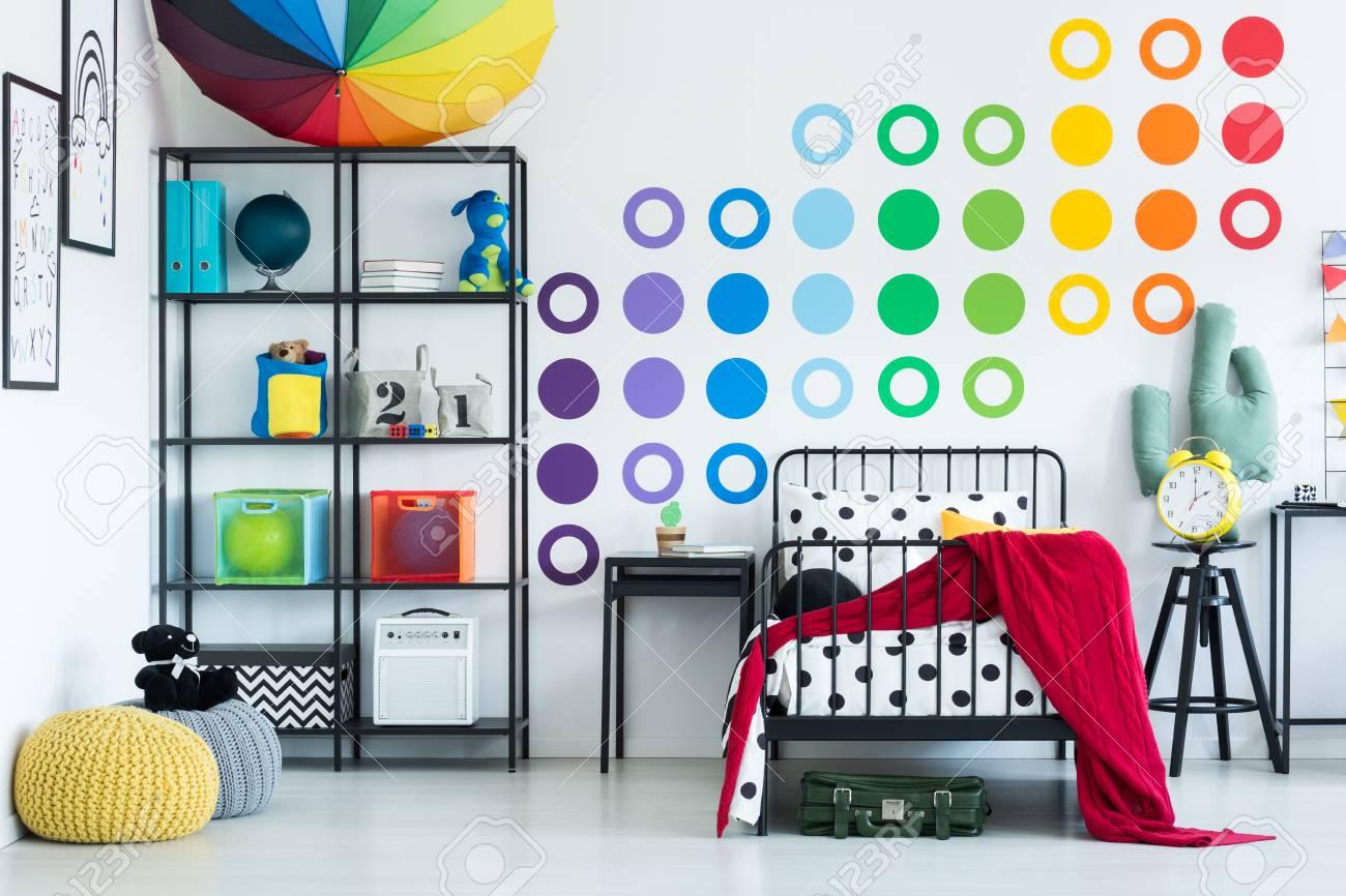Autocollant mural coloré dans la chambre d\'enfant avec horloge jaune sur  tabouret noir et pouf sur le sol
