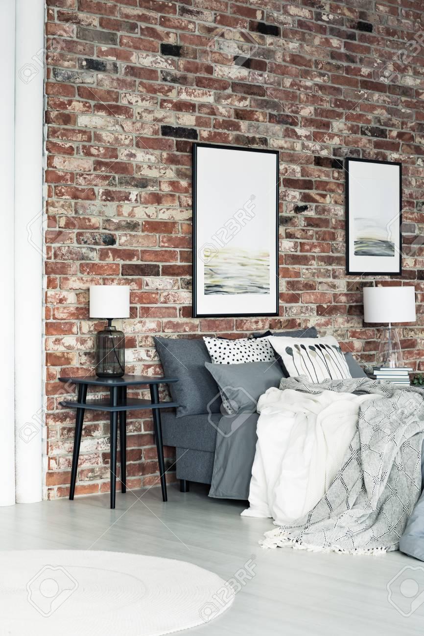 Zwei Poster Hangen An Einer Backsteinmauer Im Loft Stil Schlafzimmer