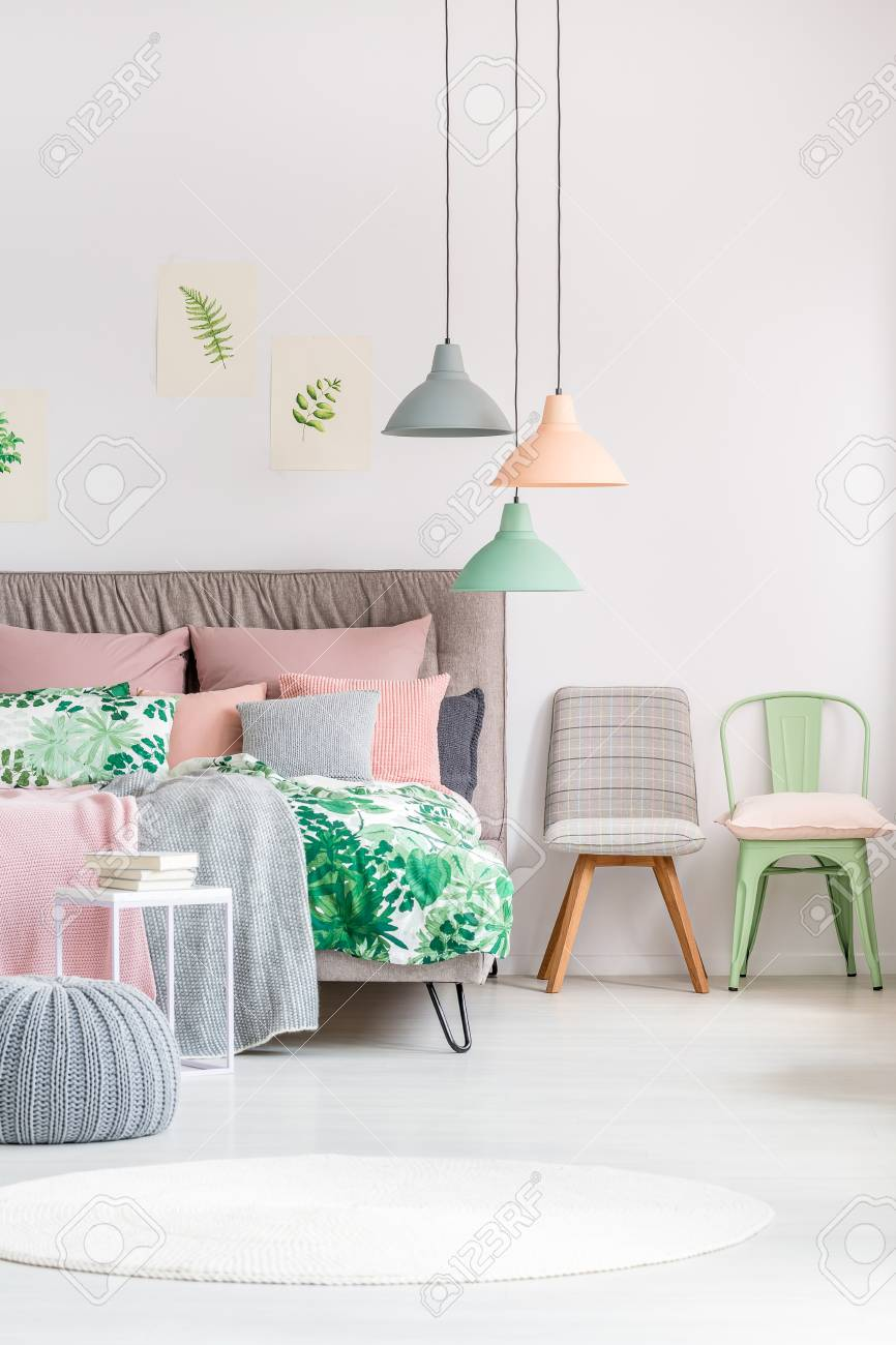Different chairs next to king-size bed with green and pink bedsheets..