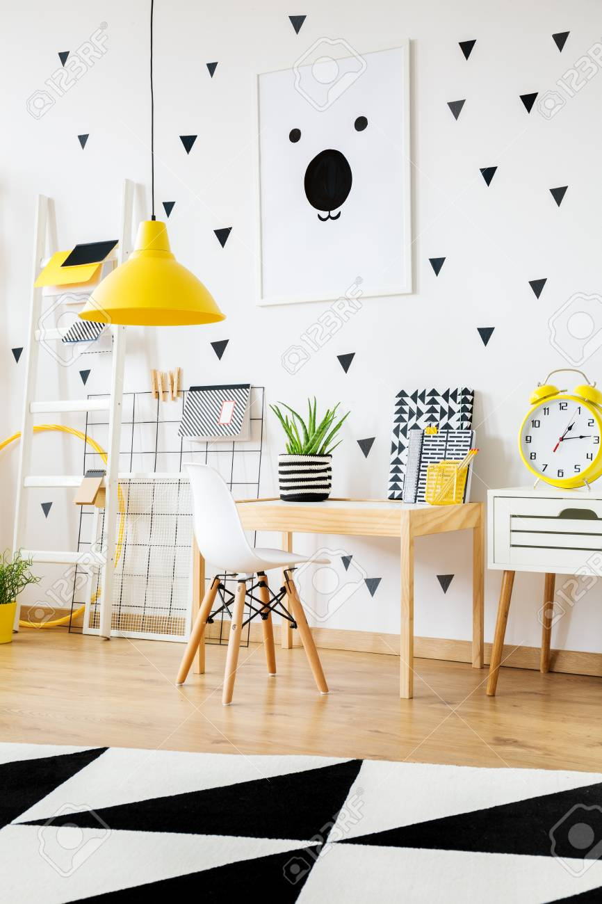 Stock Photo   Yellow Clock On White Cabinet Next To Wooden Desk And White  Chair In Contrast Color Kindergarten