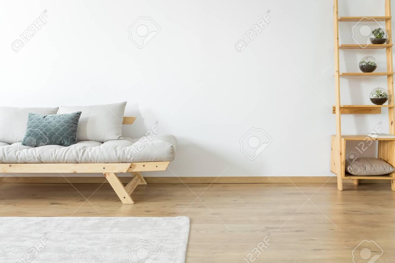 Espace de copie de mur blanc et de tapis sur le sol dans le salon beige  avec décoration sur des étagères en bois près d\'un canapé avec des oreillers