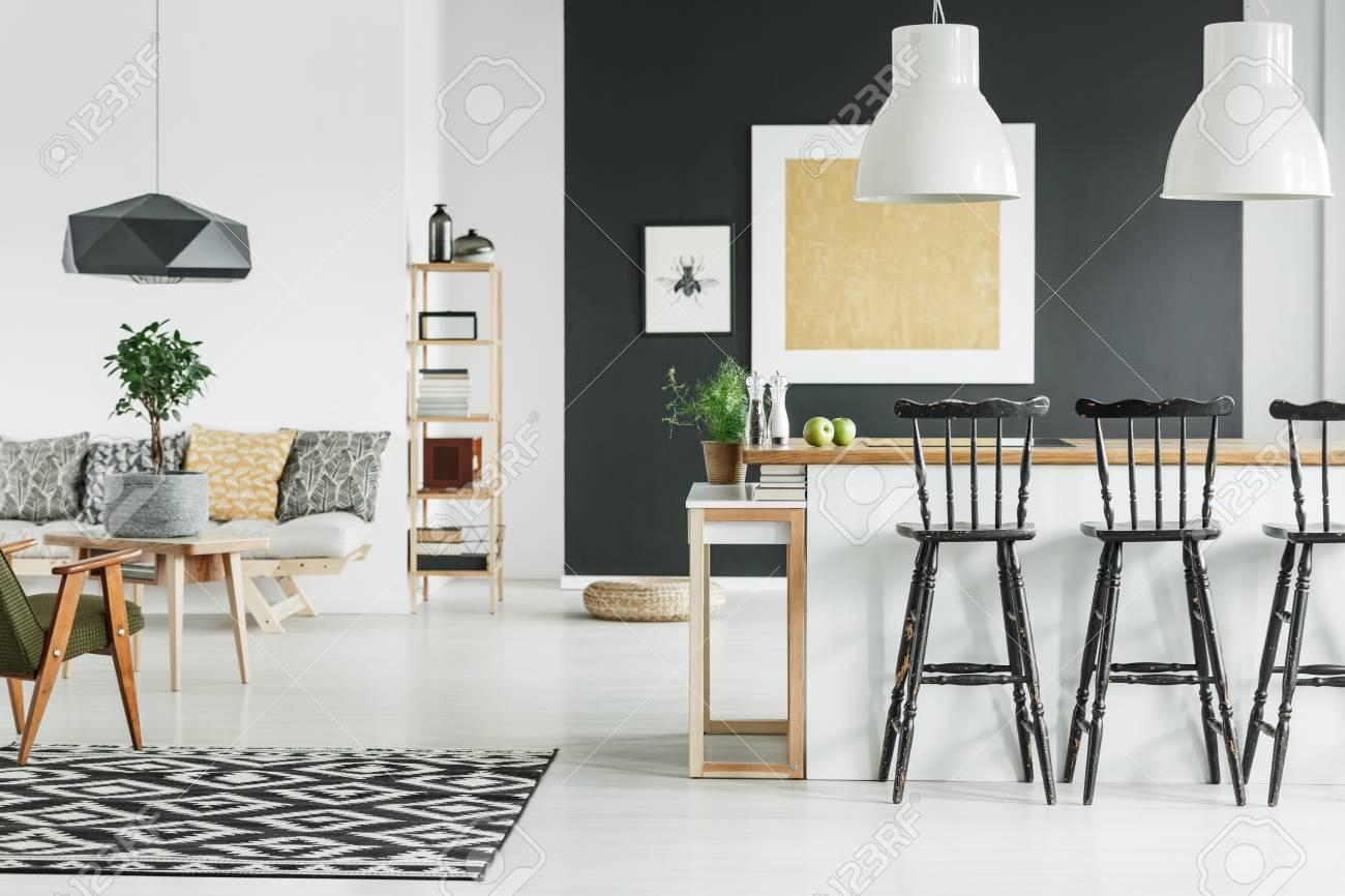 Schwarze Designerlampe über Tisch Mit Pflanze Im Topf Im Stilvollen  Wohnzimmer Mit Goldmalerei An Der Wand
