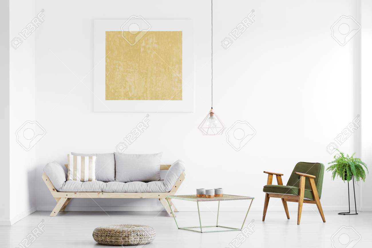 Gold Painting Above Grey Sofa In Bright Living Room With Armchair