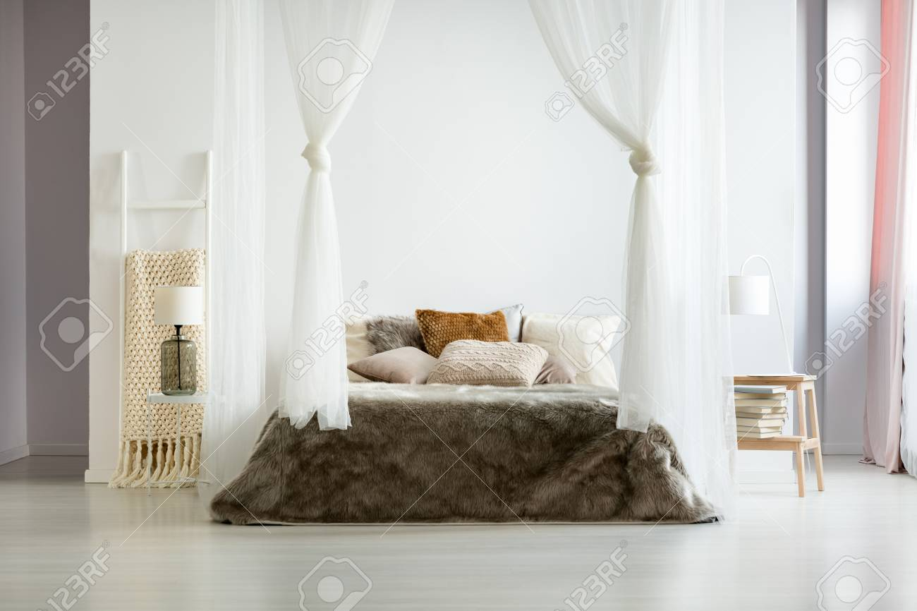 . Fur brown bedding and glass lamp in minimalist comfy bedroom