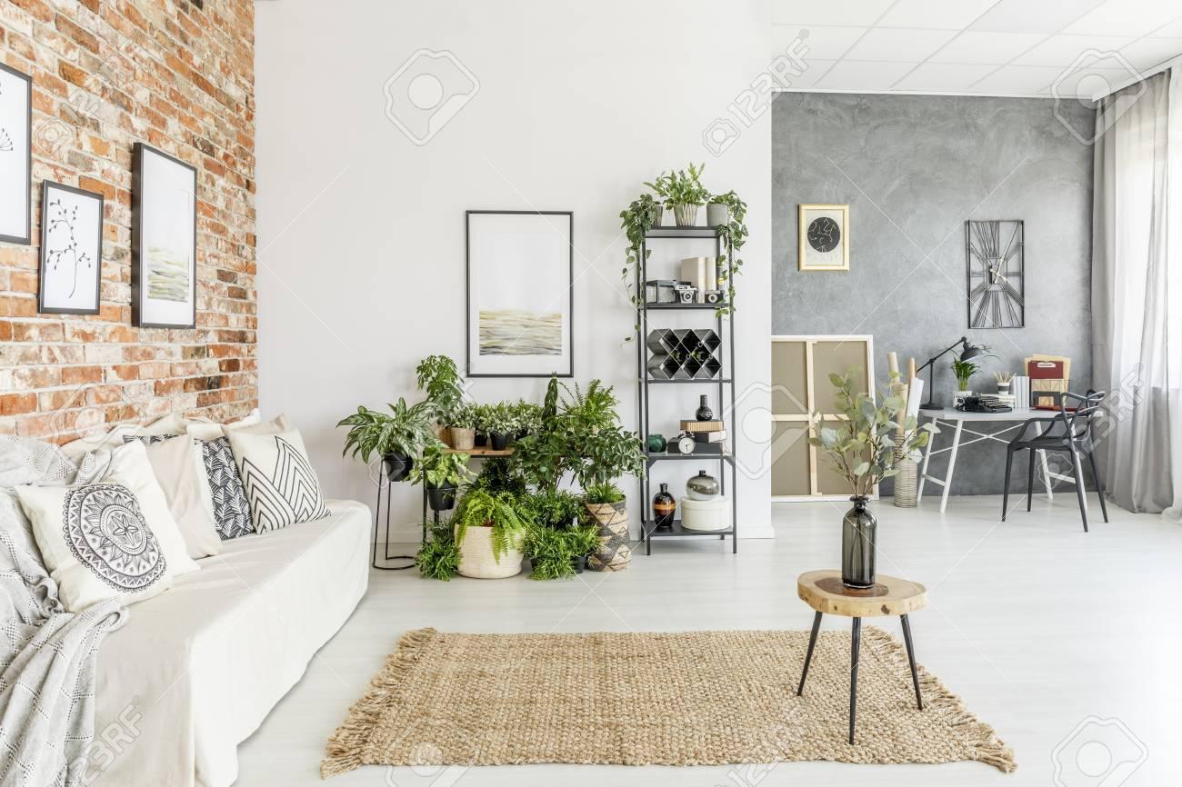 Tabouret avec vase sur tapis marron dans le salon lumineux avec canapé  blanc et plantes