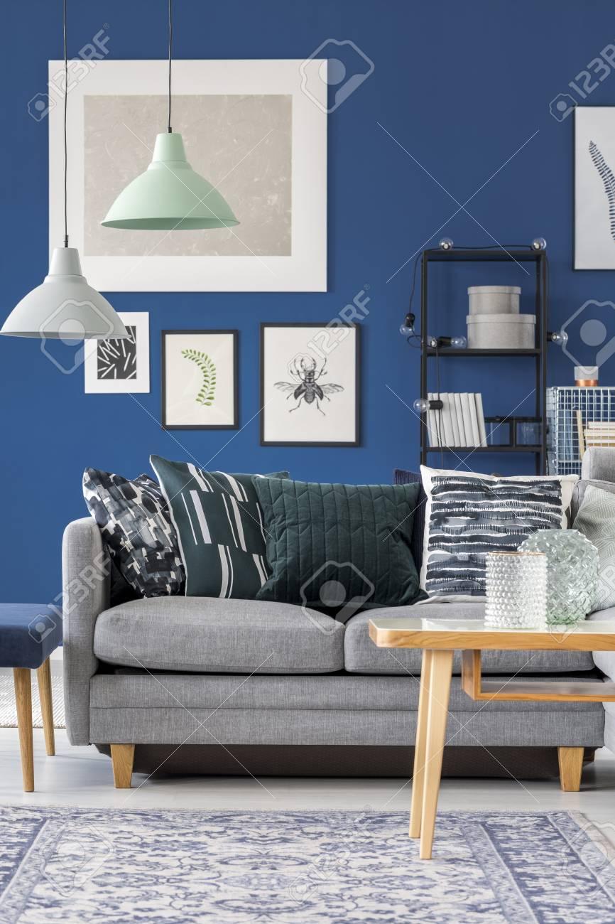 Banque Du0027images   Canapé Gris Avec Des Oreillers à Motifs Dans La Chambre  Bleu Marine Avec Galerie Du0027affiches