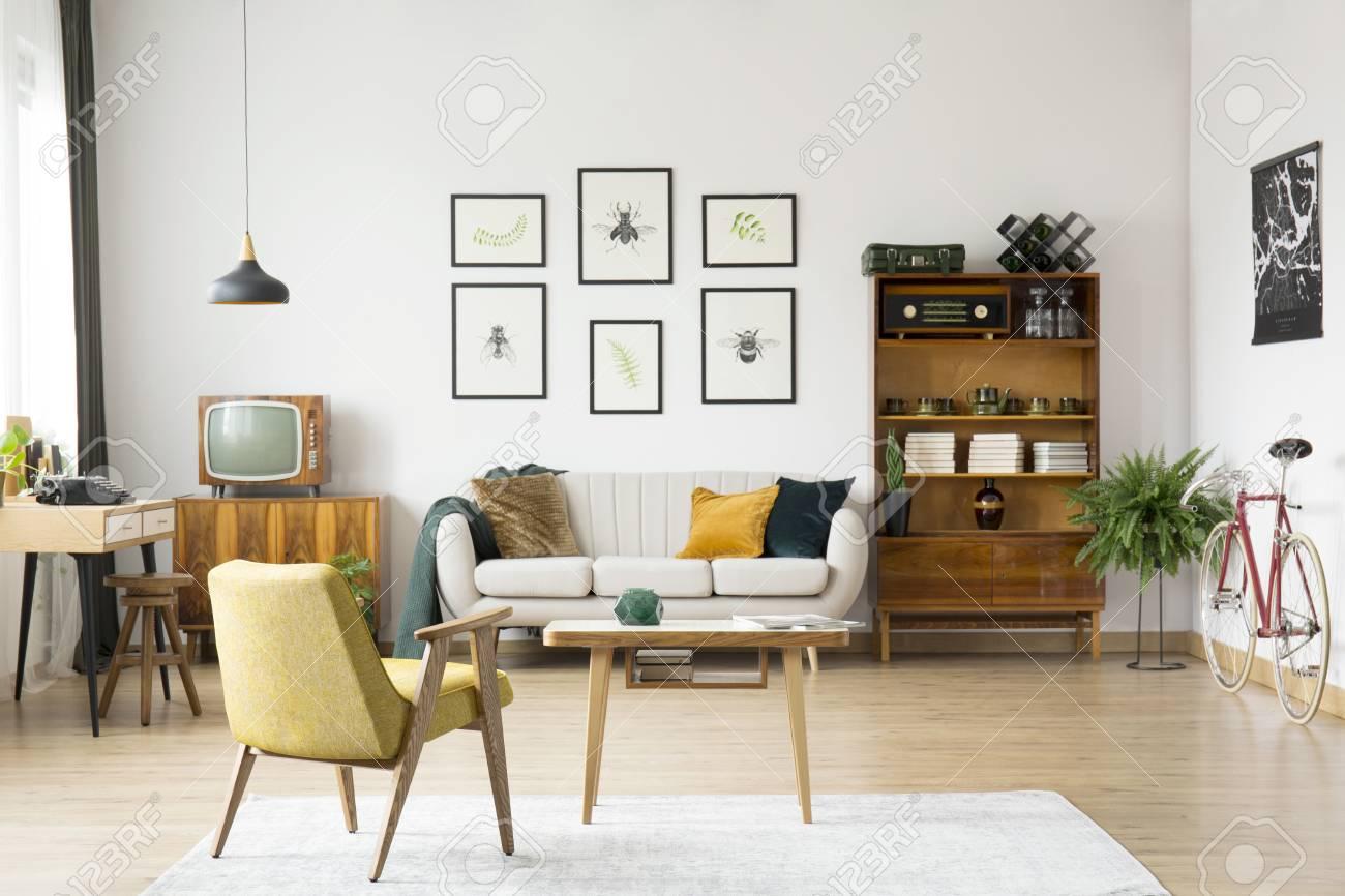 Chaise jaune à table en bois sur le tapis blanc dans le salon rétro avec  lampe sur la nappe près de canapé