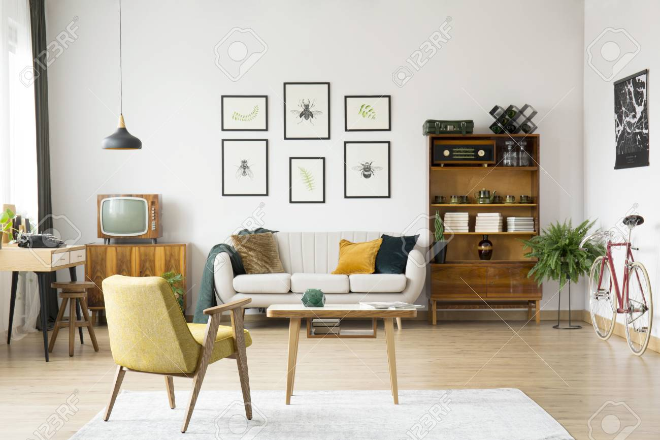 Yellow chair at wooden table on white carpet in retro living..
