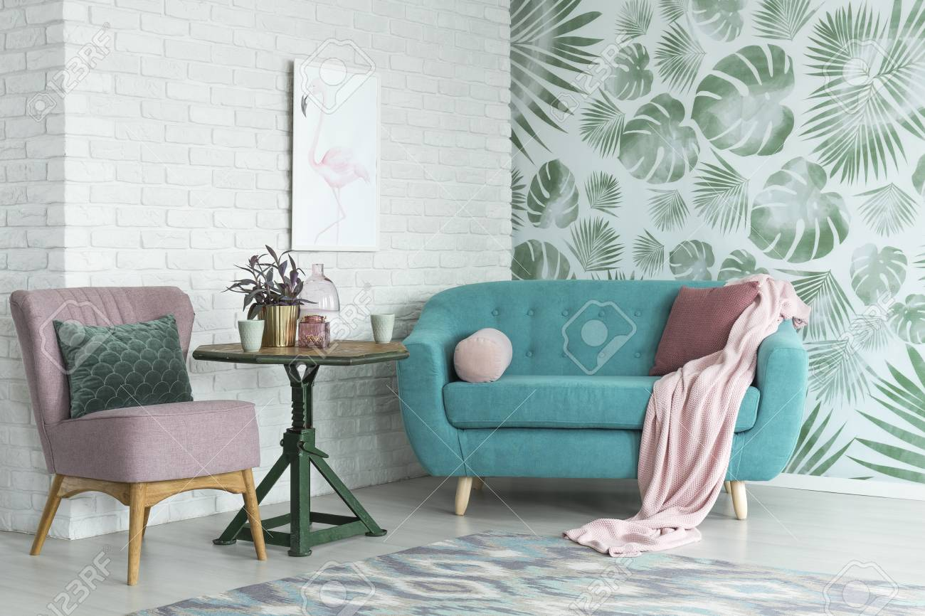 Green Table With A Plant Between Pink Chair And Blue Sofa In