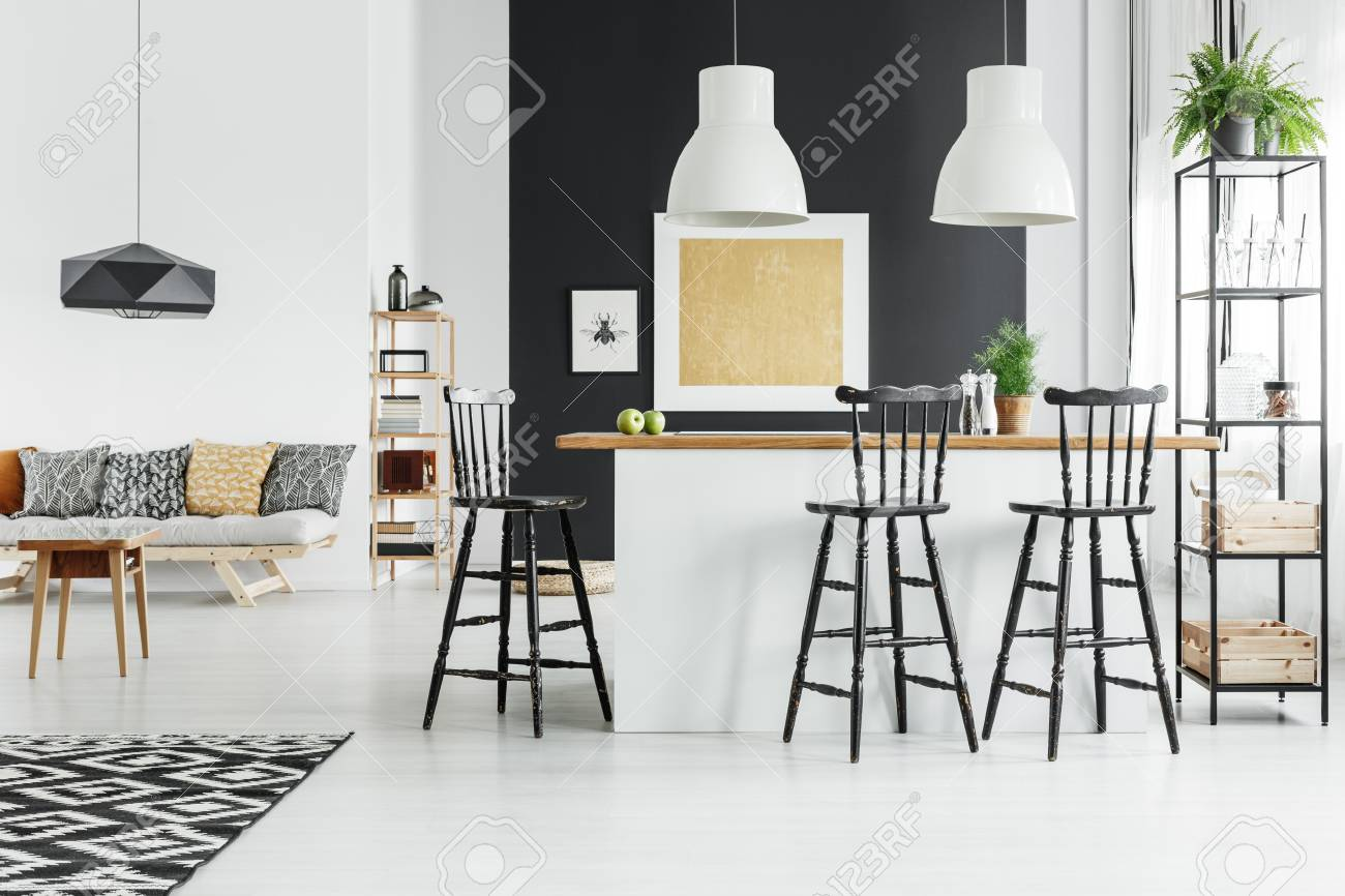 Fern on shelf in dining room with bar stools at kitchen island..
