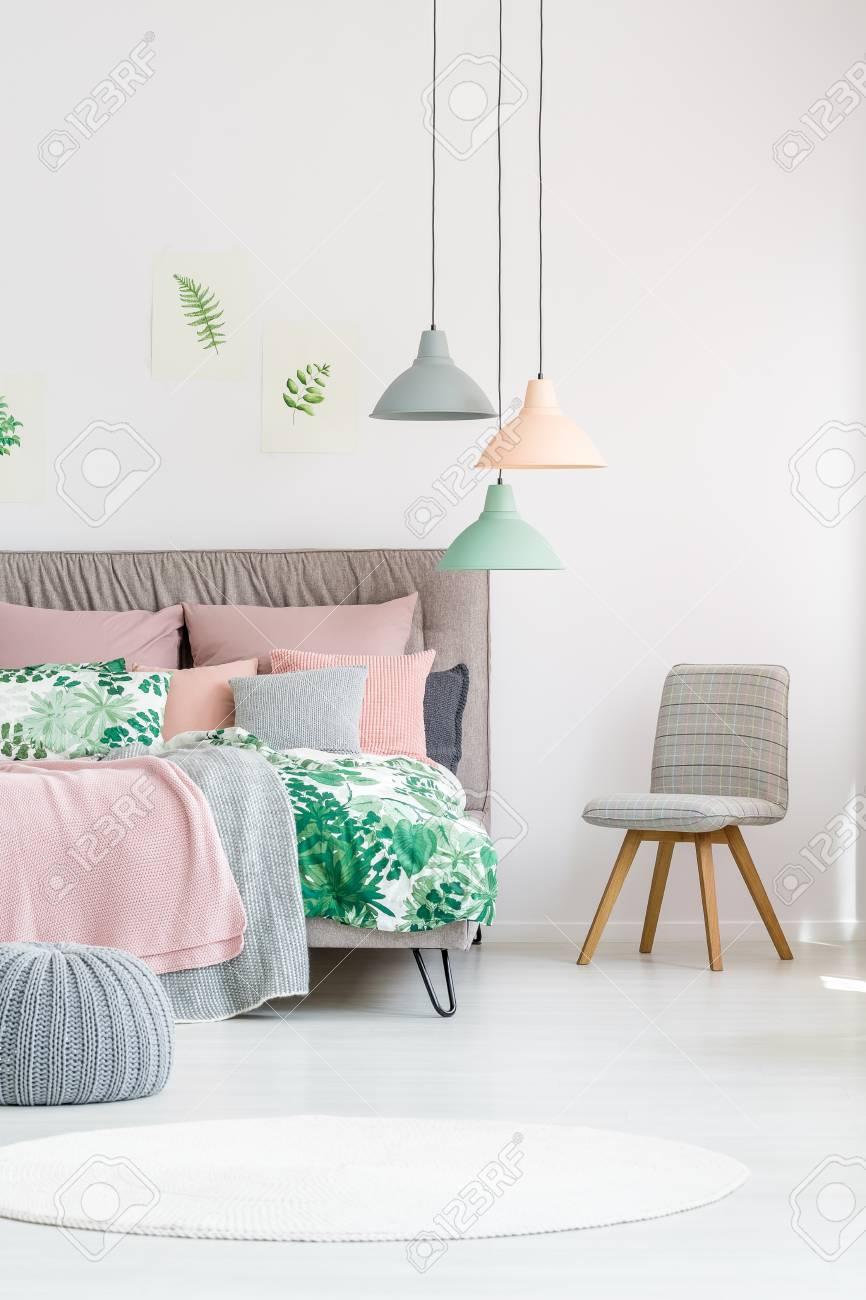 Chaise souple debout à côté du lit avec une literie rose floral et pastel  dans la chambre blanche