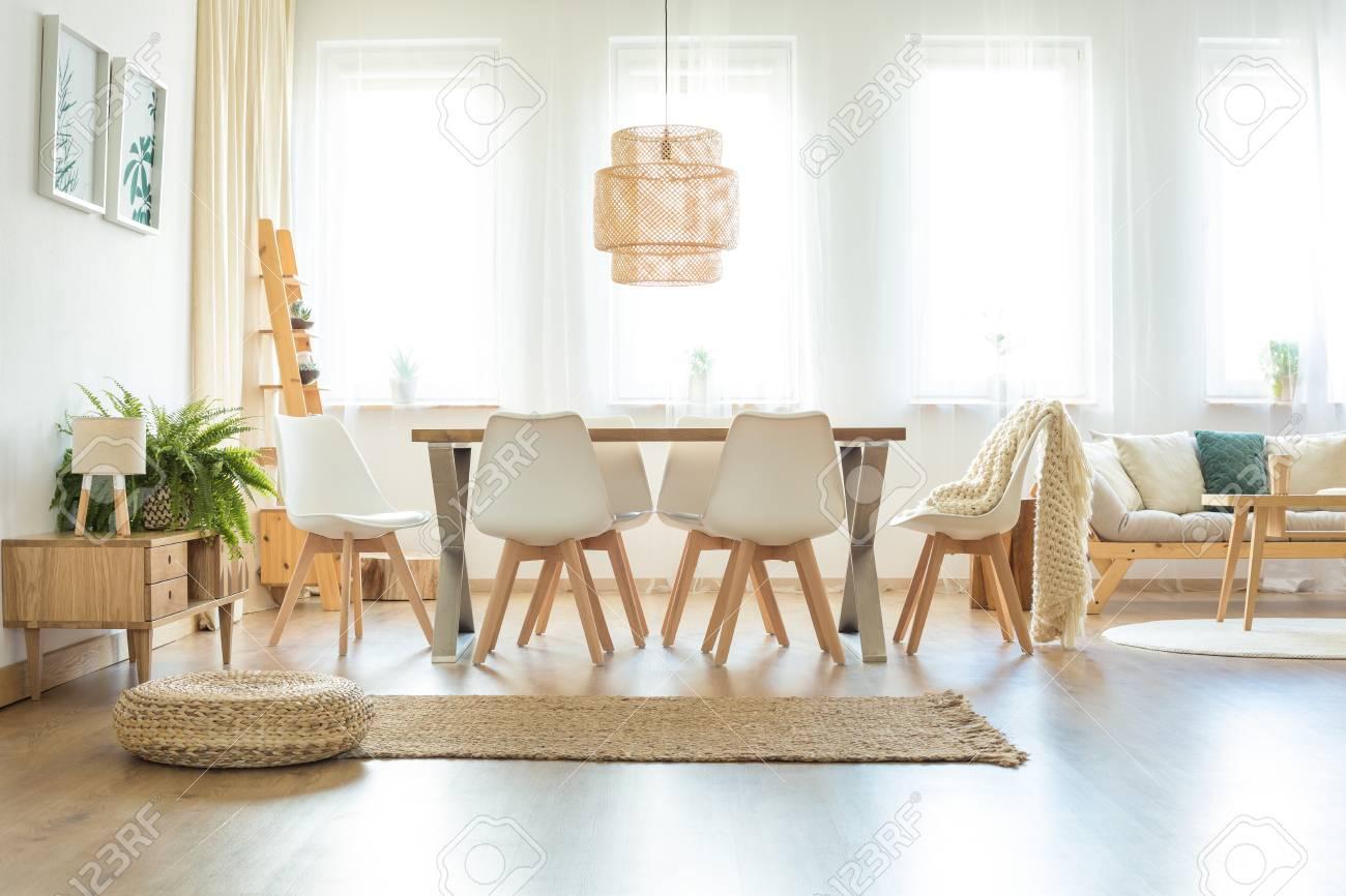 Puf y alfombra marrón en amplio comedor luminoso con lámpara sobre mesa y  sillas