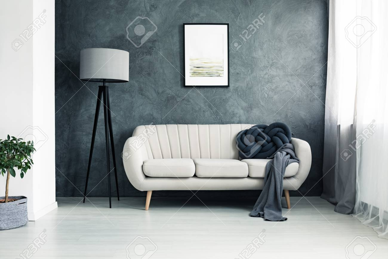 Bright couch with handmade knot cushion and grey blanket standing in a living room with lamp and poster hanging on textured wall - 90574868