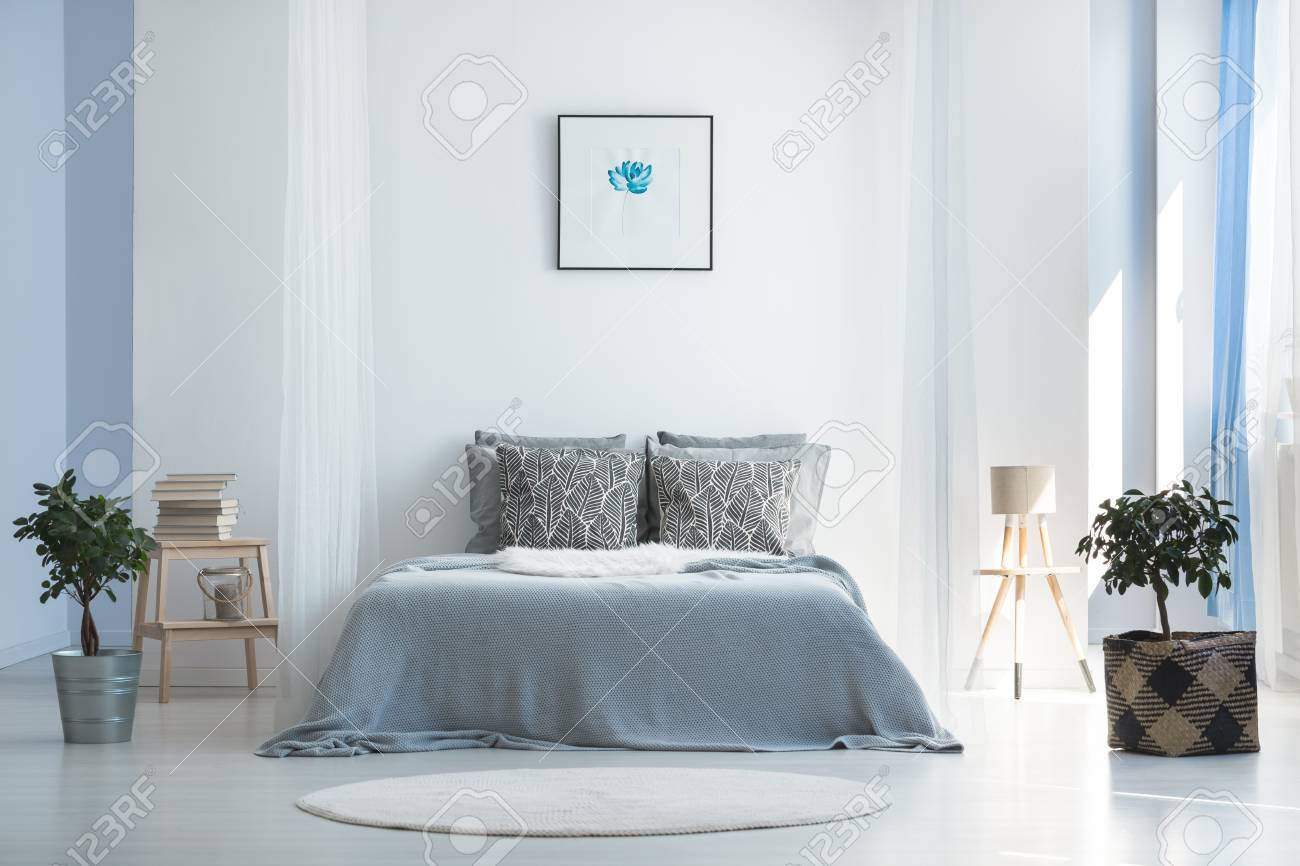 Soft Textiles And Potted Plants In Light Blue Master Bedroom Stock